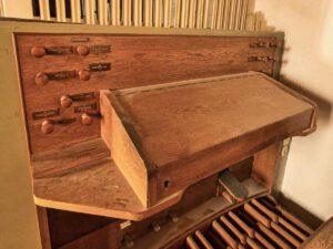 Spieltisch angebaut, Manual I Rückpositiv (Hauptwerk), Manual II Schwellwerk, Pedal. Einzige Orgelanlage unter Teck mit dem Spieltisch innerhalb des Instruments. Umfang Manuale: C – g''', Pedal C – f'. Koppeltritte. Mechanischer Jalousieschweller. Notenpult: Spieltischdeckel, Auflagebrett mit Klavierband befestigt. Breite/Höhe/Tiefe/Neigung: 623 mm, 255 mm, 63 mm, 15°. Beleuchtung Notenpult: Wandlampe. Beleuchtung Pedal: Sofitte (außer Funktion). Beleuchtung Manubrien: Wandlampe. Beleuchtung im Schwellwerk. Beleuchtung des Prospekts durch Lampen fürs Kirchenschiff. Motorschalter: Massiver Relaisschalter mit Ein- und Aus-Knopf. Kontrolllicht Motor: Glimmlicht. Steckdosen: 1x rechts zwischen Wand und Spieltisch. Elektroinstallation: Nicht sichtbar. Heizung: Gebasteltes Gestell zum Aufhängen eines Heizlüfters. Schlösser: An Gehäusetüre und Spieltischdeckel, dieses außer Betrieb. Firmenschild: Über dem 2. Manual im Stil der Registerschilder. Orgelbank: nicht verstellbar.